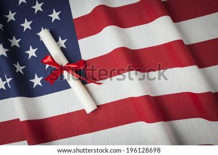 Red Ribbon Wrapped Diploma Resting on American Flag with Copy Space.