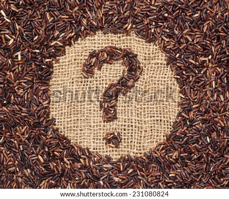 Red rice forming a question mark on burlap fabric  - stock photo