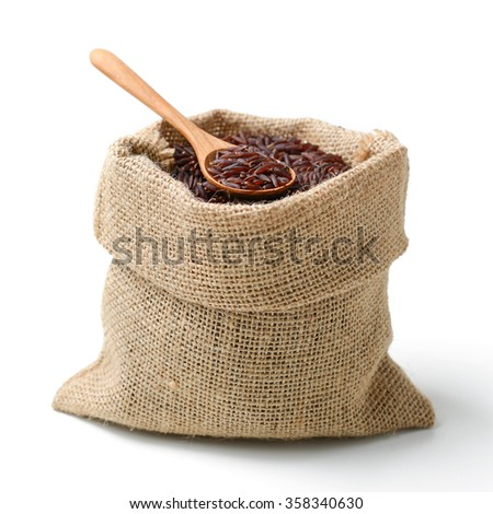 red rice in sack bag with spoon