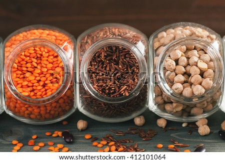 Red rice, red lentils and chickpeas in glass jars on a wooden table, closeup, selective focus - stock photo