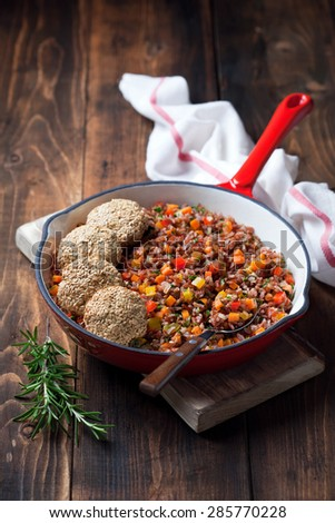 Red rice with vegetables and vegan tofu flax seeds cutlets in cast iron skillet, selective focus - stock photo