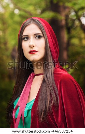 Red ridding hood with dark hair wearing a red cloak and a green dress. A lovely young girl in the forest caring a basket, just like in fairy tales - stock photo