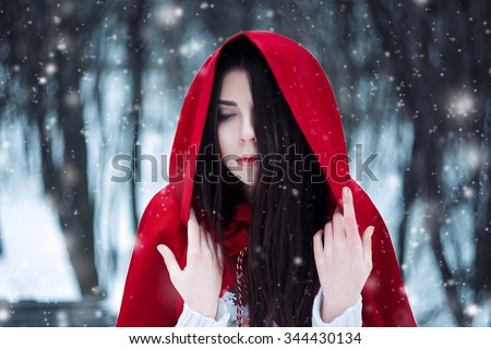 Red Riding Hood lost in the mystical snow-covered forest,fantastic shooting,fashionable toning, creative computer colors - stock photo