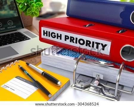 Red Ring Binder with Inscription High Priority on Background of Working Table with Office Supplies, Laptop, Reports. Toned Illustration. Business Concept on Blurred Background. - stock photo