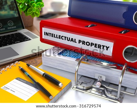 Red Ring Binder with Inscription Intellectual Property on Background of Working Table with Office Supplies, Laptop, Reports. Toned Illustration. Business Concept on Blurred Background. - stock photo