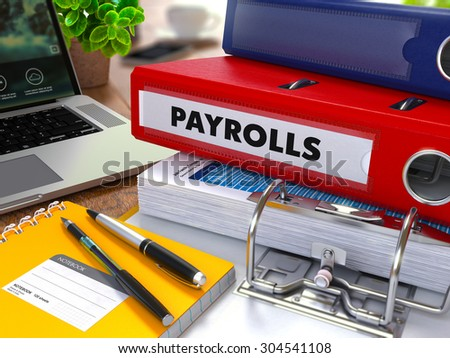 Red Ring Binder with Inscription Payrolls on Background of Working Table with Office Supplies, Laptop, Reports. Toned Illustration. Business Concept on Blurred Background. - stock photo
