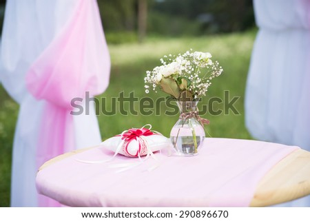 Red rings cushion on table with flowers. Wedding - stock photo