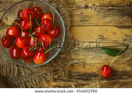 Red ripe a sweet cherry in bowl, canvas cloth on old wooden table, rustic style