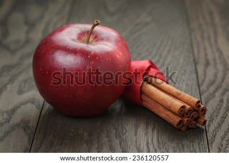 red ripe apple and cinnamon, on old oak table