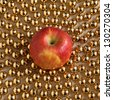 Red ripe apple and gold beads - stock photo