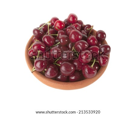 Red  ripe cherries in clay bowl isolated on white background - stock photo