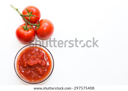 Red ripe fresh tomatoes on vine with tomato paste in a bowl isolated on white background  - stock photo
