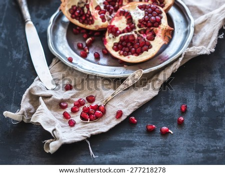 Red ripe peeled pomegranate on rustic metal plate and beige kitchen towel over dark background. Top view, copy space - stock photo