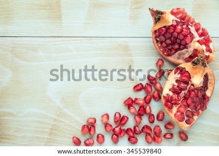 Red ripe peeled pomegranate on rustic wood board background. Top view, copy space - stock photo