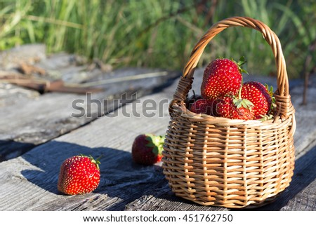 Red ripe strawberries in a wicker basket on the background of wooden boards - stock photo