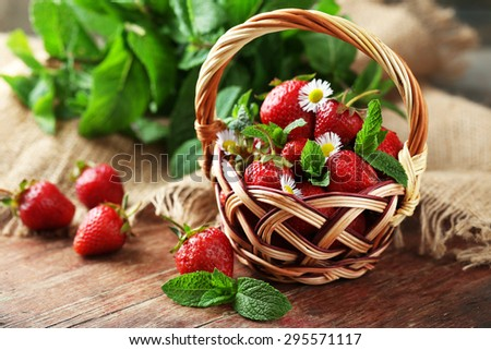 Red ripe strawberries in wicker basket, on wooden background