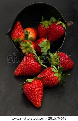 red ripe strawberries on a black slate stone trivet - stock photo