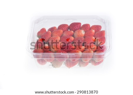 red ripe strawberry in plastic box of packaging for sale, isolated on white background