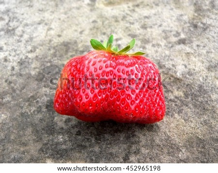 red ripe strawberry mutant outdoors on a stone - stock photo