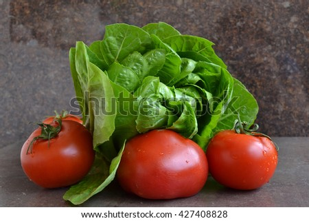 Red ripe tomatoes and fresh cos lettuce. Healthy dinner inspiration for every day. - stock photo