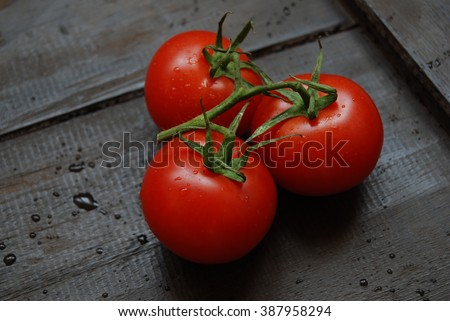 Red Ripe Tomatoes on wooden backgrounds - close-up - stock photo