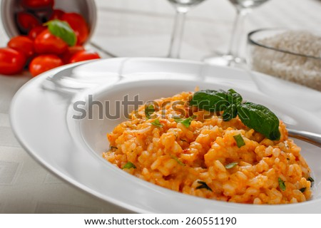 Red risotto with tomato and basil on white plate - stock photo