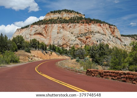 Red road leading to a huge rock on the background of deep blue sky with clouds. National park Zion. Arizona. USA  - stock photo