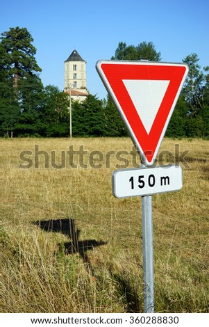 Red road sign on the field and tower of church, france
