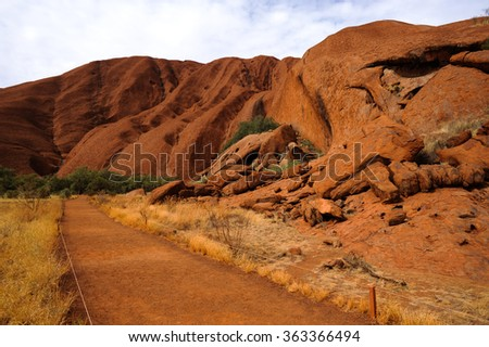 Red rock and walkway in famous attraction in middle of Australia - stock photo