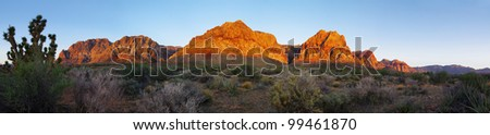 Red Rock Canyon cliffs and desert lit up by the sunrise light - stock photo