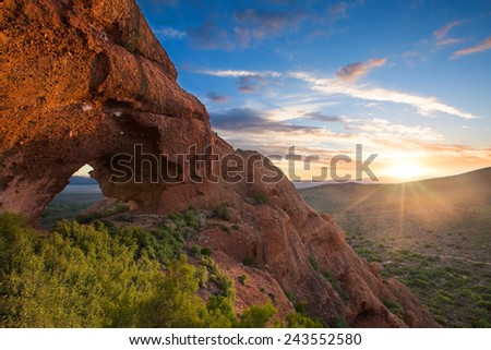 Red rock mountain with arch sunset with clouds near Calitzdorp in South Africa - stock photo