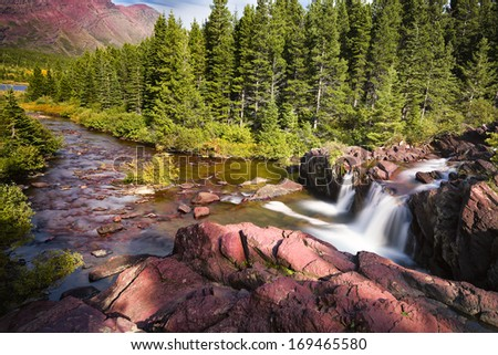 Red rocks and cascading water falls in east Glacier National Park, Montana - stock photo