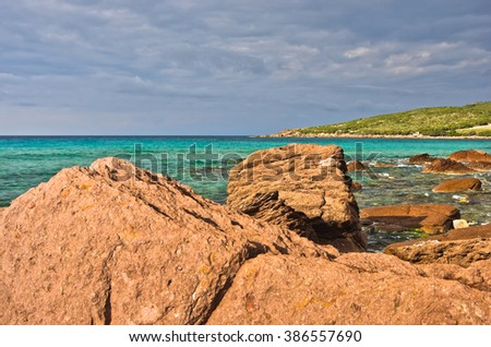 Red rocks and turquoise water at beach in San Pietro island, Sardinia, Italy - stock photo