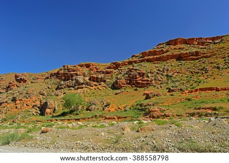 Red rocky mountains near Tamasha town, Kyrgyzstan - stock photo