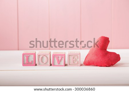 Red romantic textile heart with the word Love in pink letters on wooden alphabet blocks against a rustic wooden pink background with copyspace for your Valentine greeting - stock photo