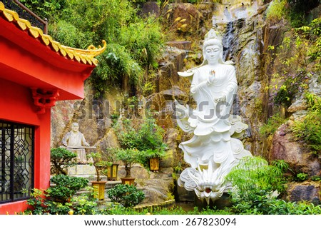 Red roof in Chinese-style and a white Buddhist statue on background of small waterfall in a garden of the Ten Thousand Buddhas Monastery in Hong Kong. Hong Kong is popular tourist destination of Asia. - stock photo