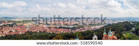 Red roofs in the city Prague. Panoramic view of Prague, Czech Republic. Summer day with blue sky with clouds in the town. Many roofs in the beautiful town Praha, Europe
