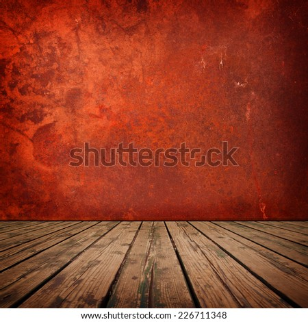 Red room. Red wall with grunge texture and rustic wooden floor in a surreal setting. - stock photo