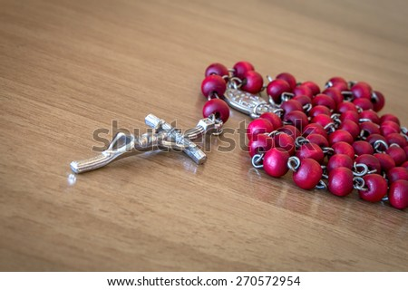 Red rosary beads with crucifix on a wooden table - stock photo