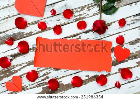 Red rose and petals with heart shape paper and copyspace on old wooden background - stock photo