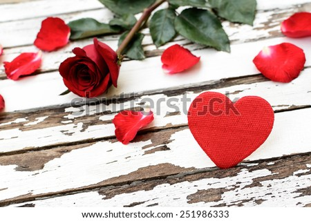 Red rose and petals with heart shape paper on wooden table