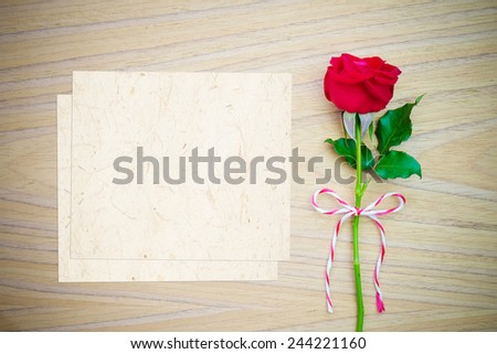 Red rose and vintage papers on wood table background - stock photo