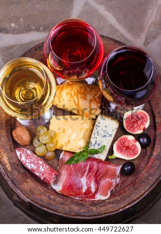 Red, rose and white glasses and bottles of wine. Cheese, fig, grape, prosciutto and bread on old wooden barrel. View from above, top studio shot of vegetables and fruits