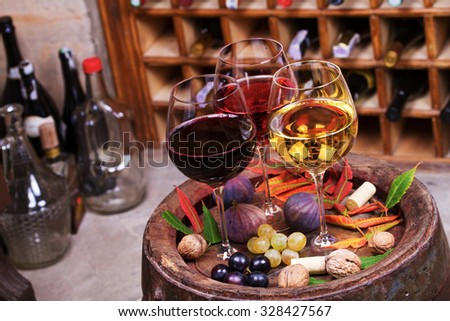 Red, rose and white glasses and bottles of wine. Grape, fig, nuts and leaves on old wooden barrel