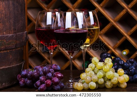 Red, rose and white glasses and bottles of wine with grapes in wine cellar