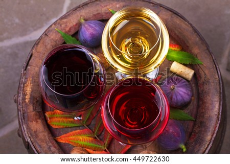 Red, rose and white glasses of wine. Grape, fig, nuts and leaves on old wooden barrel. View from above, top studio shot of vegetables and fruits