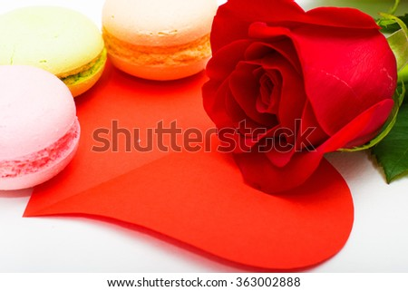 red rose, biscuits macaroons, red heart cut out of paper on white background.