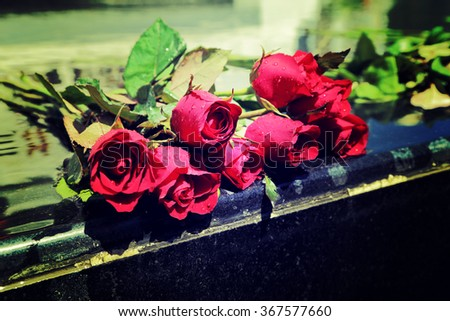 Red rose bouquet laying on mable shrine, vintage style process. - stock photo