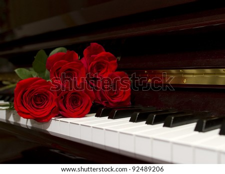 Red rose bouquet on the piano keyboard