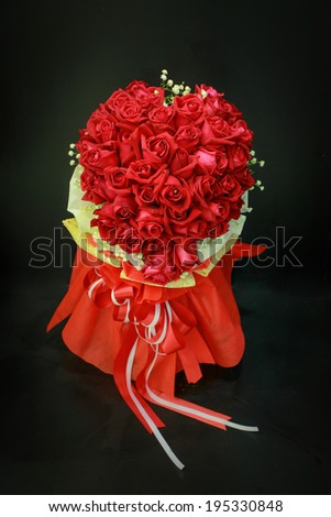 Red rose bouquet with bow tie on black background